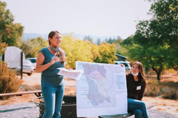 Two women hold up a map with vegatation in the background